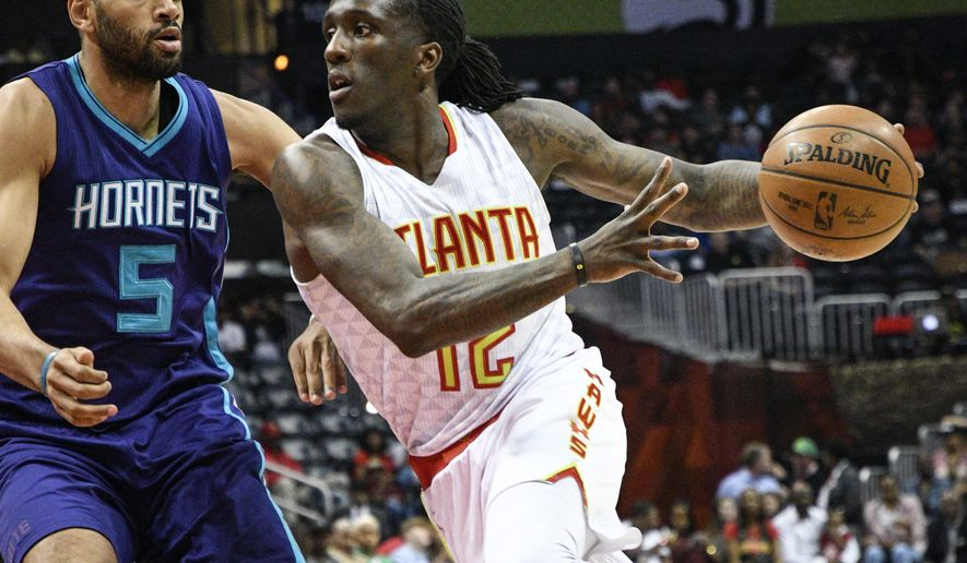 Atlanta Hawks forward Taurean Prince (12) drives to the basket as Charlotte Hornets guard Nicolas Batum (5), of France, defends during the first half of an NBA basketball game, Tuesday, April 11, 2017, in Atlanta. (AP Photo/John Amis)