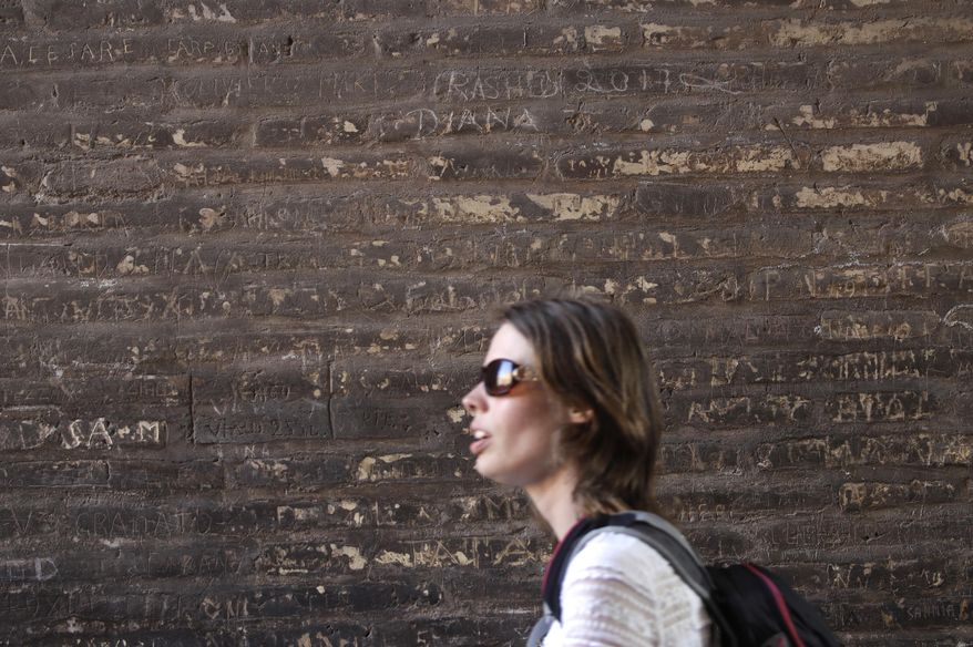 A woman walks past a writing inscribed on a wall inside the Colosseum, Tuesday, April 11, 2017. Italian police say a tourist from Ecuador has been cited for inscribing the name of his son and wife and the year, 2017, on Monday, April 10, 2017 inside the ancient Roman Colosseum. Carabinieri Major Lorenzo Iacobone said the tourist was observed in the act of vandalism by an official tour guide, who reported it to police. (AP Photo/Alessandra Tarantino)