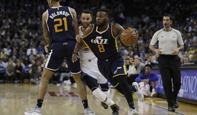 Utah Jazz guard Shelvin Mack (8) dribbles around Golden State Warriors guard Stephen Curry, center, on a screen set by Joel Bolomboy (21) during the second half of an NBA basketball game Monday, April 10, 2017, in Oakland, Calif. (AP Photo/Marcio Jose Sanchez)