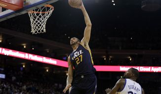 Utah Jazz center Rudy Gobert (27) dunks past Golden State Warriors forward Kevin Durant (35) during the second half of an NBA basketball game Monday, April 10, 2017, in Oakland, Calif. (AP Photo/Marcio Jose Sanchez)