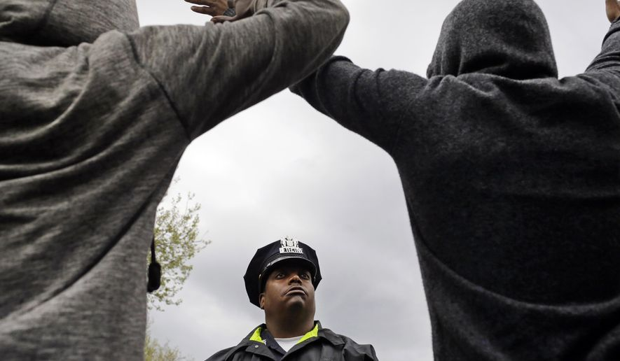 In this April 22, 2015, file photo, a member of the Baltimore Police Department stands guard outside of the department's Western District police station as men hold their hands up in protest during a march for Freddie Gray in Baltimore. In a city that became emblematic of police abuse, excessive force and callous treatment of young black men, Baltimore's mayor and commissioner say they are eager and ready to change not only the culture of law enforcement, but the practice. (AP Photo/Patrick Semansky, File)