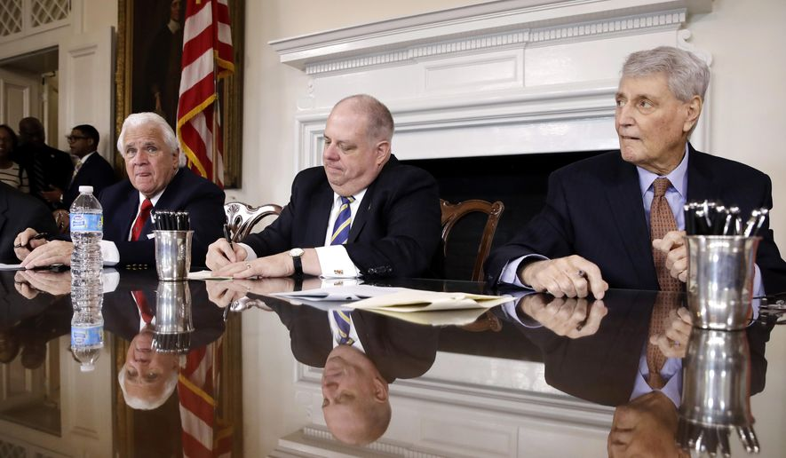 Maryland Gov. Larry Hogan, center, signs a bill between Senate President Thomas V. Mike Miller, left, and House Speaker Michael Busch during a bill signing ceremony following the state's legislative session at the Maryland State House in Annapolis, Md., Tuesday, April 11, 2017. (AP Photo/Patrick Semansky)