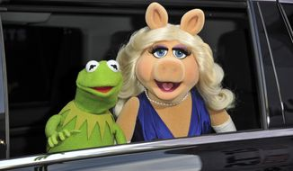 """FILE- In this March 11, 2014, file photo, Kermit the Frog, left, and Miss Piggy arrive at the World Premiere of """"Muppets Most Wanted,"""" in Los Angeles. A New York City museum is asking fans of Jim Henson's Muppets to help pay for an exhibition featuring original puppets of beloved characters like Elmo, Miss Piggy and Kermit the Frog.The Museum of the Moving Image launched a Kickstarter campaign Tuesday, April 11, 2017, seeking $40,000 to help preserve the puppets for posterity. (Photo by Richard Shotwell/Invision/AP, File)"""