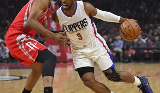 Los Angeles Clippers guard Chris Paul, right, tries to drive past Houston Rockets forward Troy Williams during the first half of an NBA basketball game, Monday, April 10, 2017, in Los Angeles. (AP Photo/Mark J. Terrill)