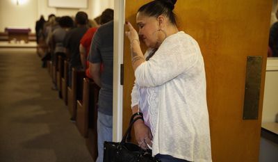 Suzanne Sullivan, 48, wipes her tears during a prayer service held to honor the shooting victims at North Park Elementary School, Monday, April 10, 2017, in San Bernardino, Calif. (AP Photo/Jae C. Hong)