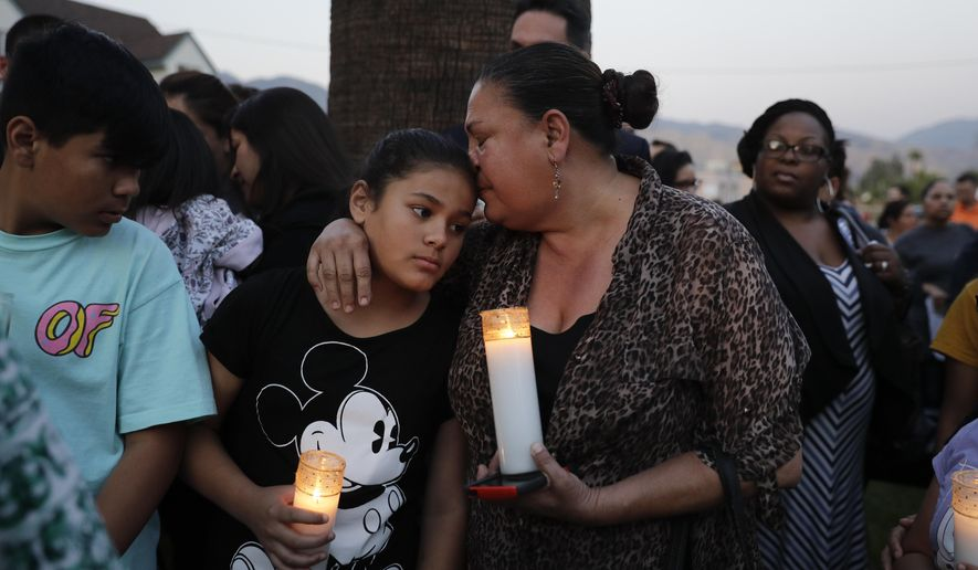 Betty Rodriguez, right, comforts her granddaughter Giselle, 11, during a prayer service held to honor the shooting victims at North Park Elementary School, Monday, April 10, 2017, in San Bernardino, Calif. A man walked into his estranged wife's elementary school classroom in San Bernardino and opened deadly fire on Monday.  (AP Photo/Jae C. Hong)