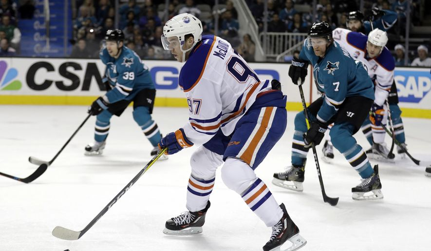 FILE - In this Dec. 23, 2016, file photo, Edmonton Oilers' Connor McDavid (97) controls the puck against the San Jose Sharks during the second period of an NHL hockey game, in San Jose, Calif. The banged-up Sharks will need to figure out how to slow down NHL scoring leader McDavid and the Oilers if they want to go on another long playoff run. (AP Photo/Marcio Jose Sanchez, File)