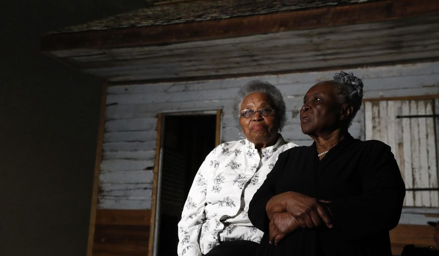 Emily Meggett, left, and Isabell Meggett Lucas sit together at the National Museum of African American History in Washington, Tuesday, April 11, 2017, in front of a slave cabin on display. Lucas was born in the two-room wood cabin that dates to the 1850's. It is believed to be one of the oldest preserved slave cabins in the U.S. (AP Photo/Carolyn Kaster)