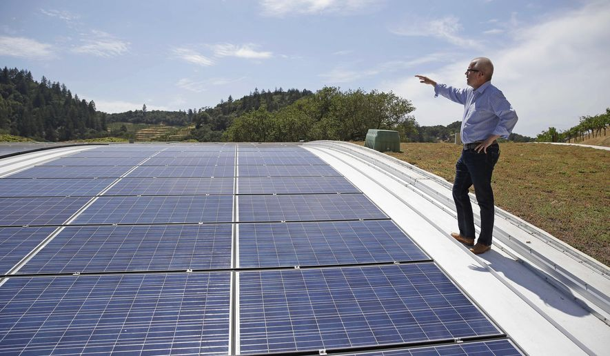 FILE - In this file photo taken July 16, 2014, Christian Oggenfuss stands near solar panels on top of the living roof at the Odette Estate winery in Napa, Calif. A new estimate from the U.S. government shows that California met about half of the state's electricity demand for three hours on March 11, 2017--the state's goal is for 50 percent of all electricity to come from renewable sources by 2030. (AP Photo/Eric Risberg, File)