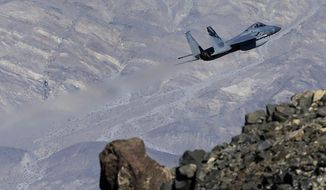 In this Feb. 28, 2017, photo, an F-15C Eagle from the California Air National Guard, 144th Fighter Wing, flies out of the nicknamed Star Wars Canyon over Death Valley National Park, Calif. Military jets roaring over national parks have long drawn complaints from hikers and campers. But in California's Death Valley, the low-flying combat aircraft skillfully zipping between the craggy landscape has become a popular attraction in the 3.3 million acre park in the Mojave Desert, 260 miles east of Los Angeles. (AP Photo/Ben Margot)