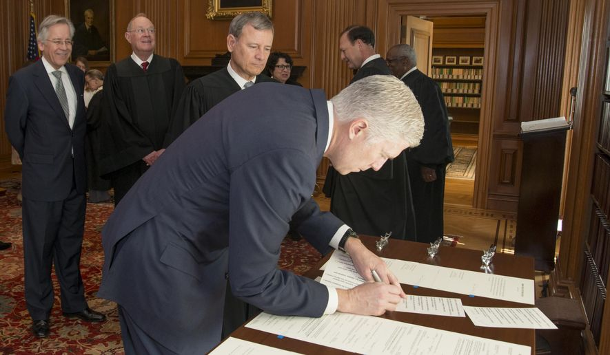 In this photo provided by the Public Information Office Supreme Court of the U.S., Chief Justice John Roberts, Jr., and fellow justices watch as Neil Gorsuch signs the Constitutional Oath after Roberts administered the Constitutional Oath in a private ceremony, Monday, April 10, 2017, in the Justices' Conference Room at the Supreme Court in Washington. How do you keep a new Supreme Court justice's head from getting too big? Start by making him take notes and answer the door at the justices' private meetings. Then, remind him he speaks last at those discussions. Finally, assign him the job of listening to gripes about the food at the court's cafeteria.  (Franz Jantzen/Public Information Office Supreme Court of the U.S. via AP)