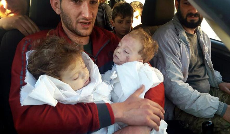 In this Tuesday April 4, 2017, file photo, Abdel Hameed Alyousef, 29, holds his twin babies who were killed during a suspected chemical weapons attack, in Khan Sheikhoun in the northern province of Idlib, Syria. (Alaa Alyousef via AP, File)