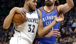 Minnesota Timberwolves' Karl-Anthony Towns, left, drives around Oklahoma City Thunder's Steven Adams during the first half of an NBA basketball game Tuesday, April 11, 2017, in Minneapolis. (AP Photo/Jim Mone)