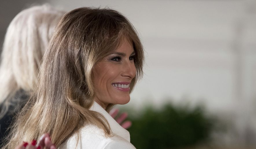 U.S. first lady Melania Trump smiles as she is recognized by President Donald Trump as he speaks at a women's empowerment panel, in the East Room of the White House in Washington, in this Wednesday, March 29, 2017, file photo. Mrs. Trump on Wednesday, April 12, 2017, accepted an apology and damages from the publisher of the Daily Mail newspaper for reporting rumors about her time as a model. (AP Photo/Andrew Harnik, File)