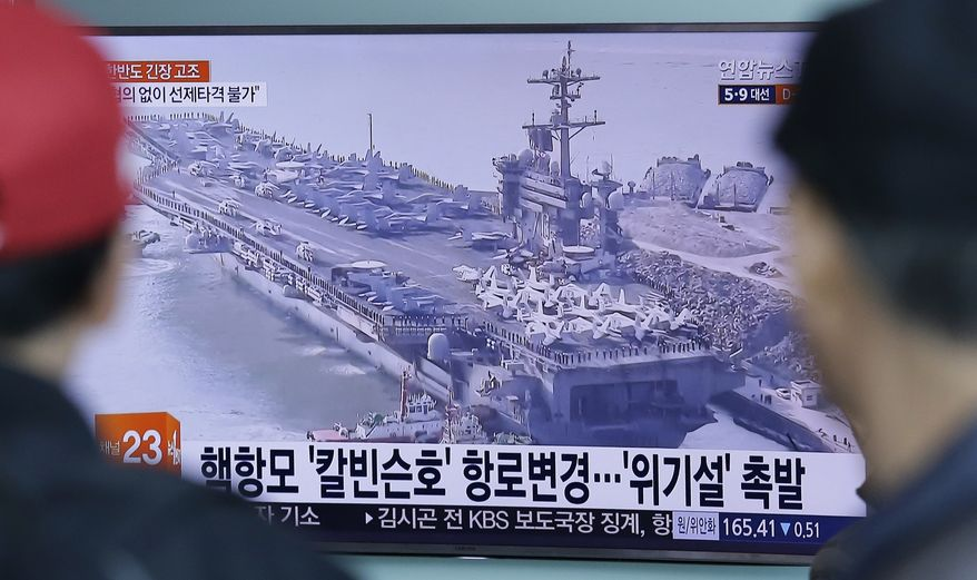 """People watch a TV news program showing a file image of the USS Carl Vinson aircraft carrier at Seoul Railway Station in Seoul, South Korea, Wednesday, April 12, 2017. North Korea's parliament convened Tuesday amid heightened tensions on the divided peninsula, with the United States and South Korea conducting their biggest-ever military exercises and the USS Carl Vinson aircraft carrier heading to the area in a show of American strength. The signs read """"The USS Carl Vinson aircraft carrier changes route"""". (AP Photo/Ahn Yooung-joon)"""