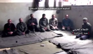 "This frame grab from video provided by the government-controlled Syrian Central Military Media, shows Syrian rebels sitting inside a room before release as part of a deal to evacuate over 10,000 residents from Madaya and Zabadani, two opposition-held areas near Damascus, and the two rebel-besieged villages of Foua and Kfarya, in Idlib province, northern Syria, Wednesday, April 12, 2017. Syria's government and rebels exchanged some 30 prisoners and nine bodies, part of a larger agreement to evacuate four besieged areas in different parts of the country, activists and officials said Wednesday. The Arabic words above read:""Handing over the fighter prisoners as part of the exchange deal."" (Syrian Central Military Media, via AP)"