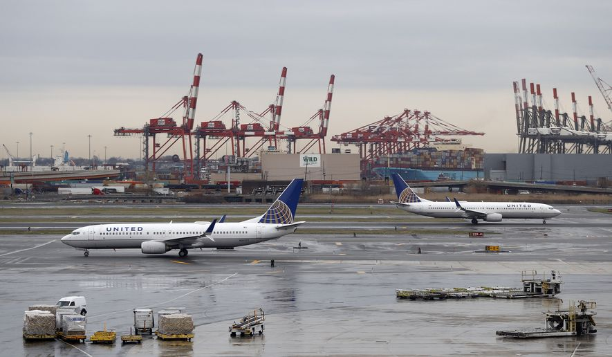 Cranes from the Port of Newark give backdrop to United Airlines planes taxing at Newark Liberty International Airport, Wednesday, April 12, 2017, in Newark, N.J. (AP Photo/Julio Cortez)