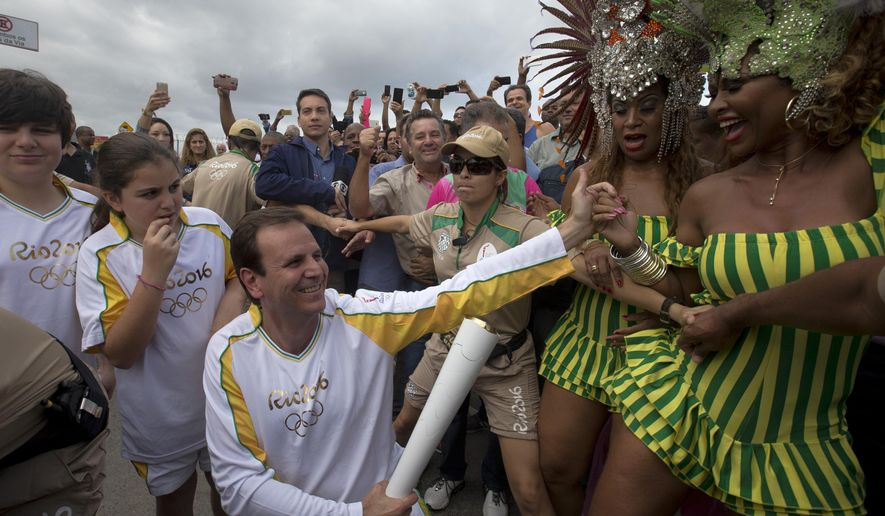 File - In this Aug. 3, 2016 file photo, Rio de Janeiro's Mayor Eduardo Paes, center, holds the Olympic torch, while members of the Mangueira samba school dance, in Rio de Janeiro, Brazil. The former Rio de Janeiro Mayor, the moving force behind organizing last year's Olympics, is being investigated for accepting at least 15 million Brazil reals ($5 million) in payments to facilitate construction projects tied to the Games. (AP Photo/Silvia Izquierdo, File)