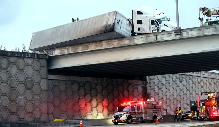 CORRECTS TO TOW TRUCK WORKER, NOT DRIVER - A tractor trailer dangles off the Congress Avenue overpass over I-95 early Wednesday, April 12, 2017, in West Palm Beach, Fla. The Florida Highway Patrol says a tow truck worker fell to his death from an overpass on Interstate 95 while helping to upright an overturned tractor trailer.  (Lannis Waters/Palm Beach Post via AP)