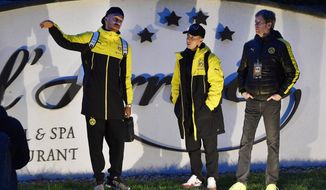 Dortmund's Pierre-Emerick Aubameyang, left, talks to teammates after a window of Dortmund's team bus was damaged after an explosion before the Champions League quarterfinal soccer match between Borussia Dortmund and AS Monaco in Dortmund, western Germany, Tuesday, April 11, 2017.  (AP Photo/Martin Meissner)