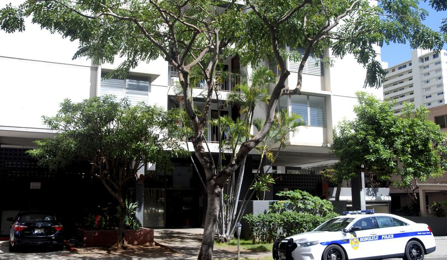 A police car sits outside an apartment building where human remains were found in Honolulu's Waikiki neighborhood, Wednesday, April 12, 2017. Police arrested a 26-year-old man Tuesday on suspicion of second-degree murder after human remains were found in his Waikiki apartment. (AP Photo/Jennifer Sinco Kelleher)