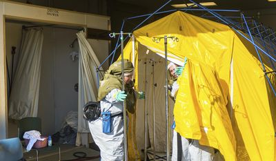 FILE - In this Oct. 21, 2016 file photo emergency workers clean various items inside a decontamination tent at Mosaic Life Care, in Atchison, Kan. Federal investigators say Human error and problems with design and labeling led to the release of a large chemical cloud over the city that sent more than 140 people to the hospital last year. The chemical release from MGP Ingredients in Atchison, occurred when a delivery truck driver inadvertently unloaded sulfuric acid into a tank that contained sodium hypochlorite. (Dougal Brownlie/The St. Joseph News-Press via AP File)