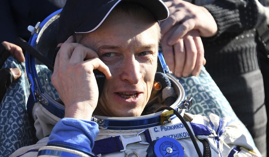 Russian cosmonaut Sergey Ryzhikov uses a sat phone shortly after landing near Dzhezkazgan, Kazakhstan Monday, April 10, 2017, on the treeless Central Asian steppes Russia's Soyuz MS-02 space capsule carrying the International Space Station (ISS) crew of Andrei Borisenko and Sergey Ryzhykov of Russia and NASA astronaut Robert Shane Kimbrough landed in a remote area in Kazakhstan. (Kirill Kudryavtsev/Pool photo via AP)