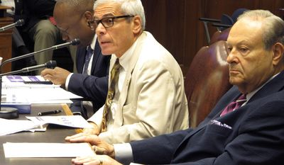 Higher Education Commissioner Joseph Rallo, center, answers questions from House budget committee members while Board of Regents Chairman Richard Lipsey, right, listens, on Wednesday, April 12, 2017, in Baton Rouge, La. (AP Photo/Melinda Deslatte)