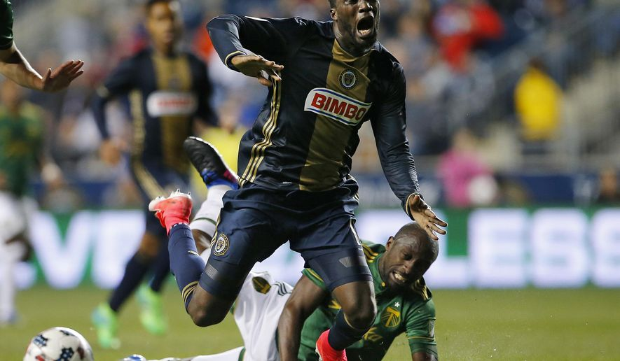 FILE - In this April 8, 2017, file photo, Philadelphia Union forward C.J. Sapong gets tangled up with Portland Timbers midfielder Lawrence Olum during the second half of an MLS soccer match in Chester, Pa. The Union are struggling with no wins, three losses and a pair of draws. Their winless streak spans 12 regular-season MLS games dating back to last season. (AP Photo/Rich Schultz, File)