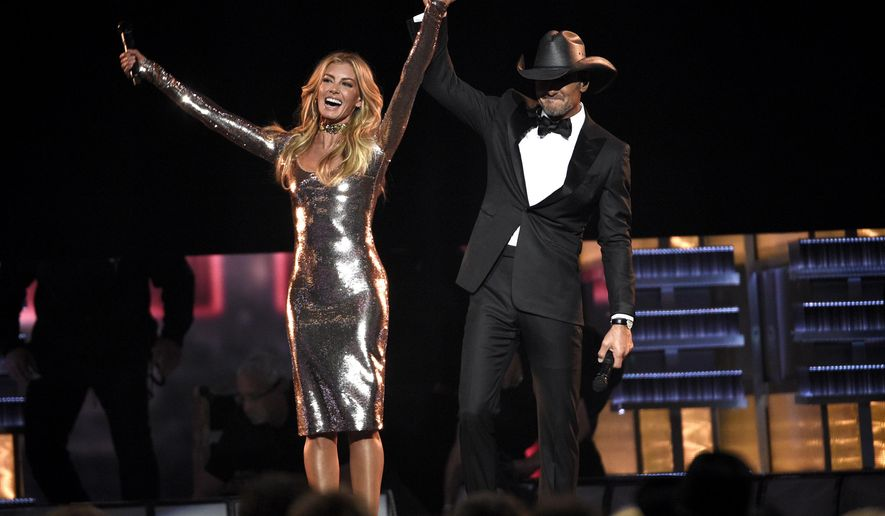 "FILE - In this April 2, 2017 photo, Faith Hill, left, and Tim McGraw appear after a performance of  ""Speak To A Girl"" at the 52nd annual Academy of Country Music Awards in Las Vegas. The country couple with movie star glamour has sold over 63 million albums in the U.S. between their two careers, has earned two Grammys for duets they sang together and has three children. This year, they are releasing their first-ever duet album together and started their third installment of their highly successful Soul2Soul World tour on April 7. (Photo by Chris Pizzello/Invision/AP, File)"