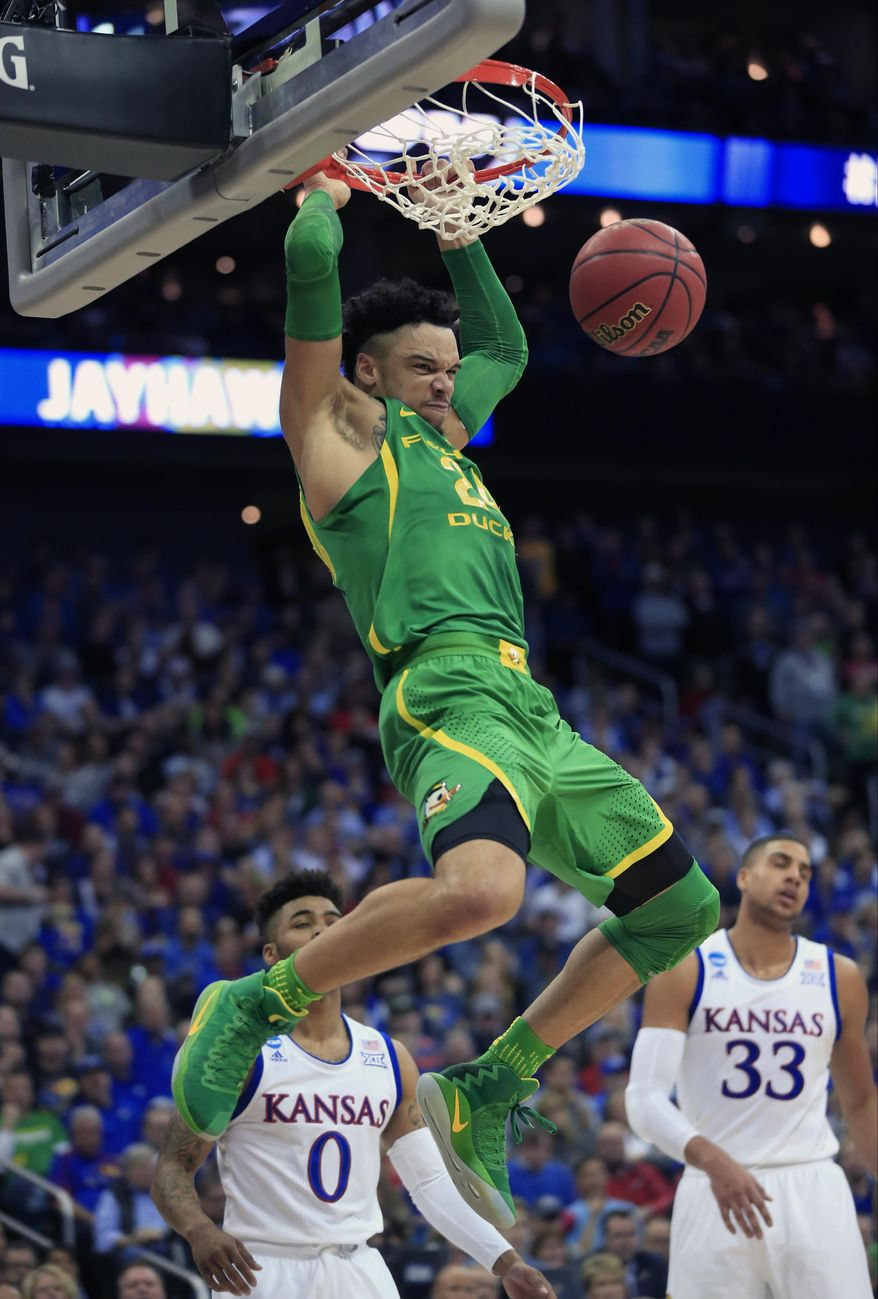 FILE- In this March 25, 2017, file photo, Oregon forward Dillon Brooks (24) dunks the ball over Kansas defenders Frank Mason III (0) and Landen Lucas (33) during the first half of a regional final of the NCAA men's college basketball tournament in Kansas City, Mo. Brooks has announced that he will declare for the NBA draft. (AP Photo/Orlin Wagner, File)