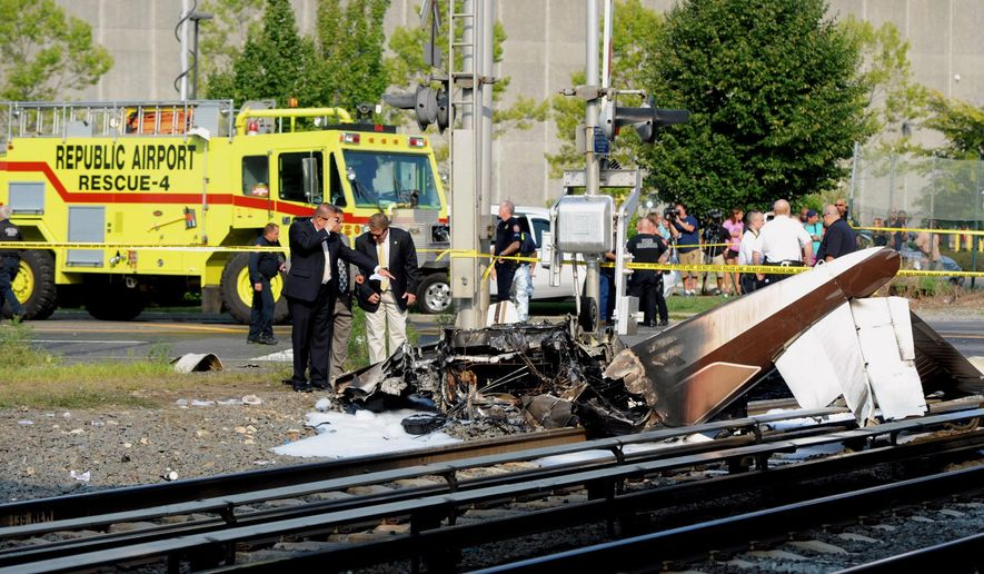 FILE- In this Aug. 16, 2015 file photo, investigators examine the scene where one person died and another was injured in the crash of a single-engine plane on Long Island Rail Road tracks on the line between Bethpage and Hicksville, NY. As a result of this crash, the Federal Aviation Administration now regularly check the accuracy of its radar video maps after an air traffic controller directed the pilot with engine trouble to a closed airport moments before the plane went down. (James Carbone/Newsday via AP, File)