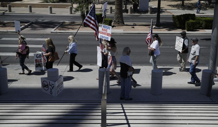 People march in support of defendants on trial in federal court, Wednesday, April 12, 2017, in Las Vegas. A federal jury in Las Vegas heard closing arguments in the trial of six men accused of wielding weapons to stop federal agents from rounding up cattle near Nevada rancher Cliven Bundy's property in 2014. (AP Photo/John Locher)
