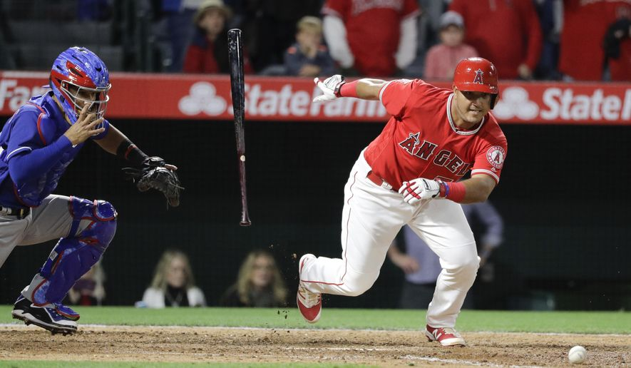 Los Angeles Angels' Carlos Perez, right, hits a walk-off bunt to win the game against the Texas Rangers during the 10th inning of a baseball game, Tuesday, April 11, 2017, in Anaheim, Calif. The Angels won 6-5. (AP Photo/Jae C. Hong)r