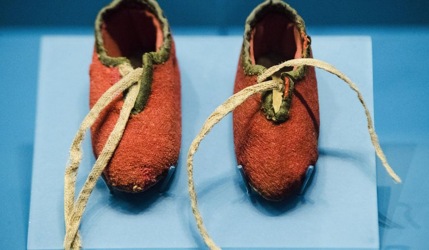 This Tuesday, April 4, 2017, photo shows a newborn's shoes made from a British red coat brought back at the end of the Revolutionary War and preserved through generations of descendants of a Massachusetts soldier, at the Museum of the American Revolution in Philadelphia. (AP Photo/Matt Rourke)