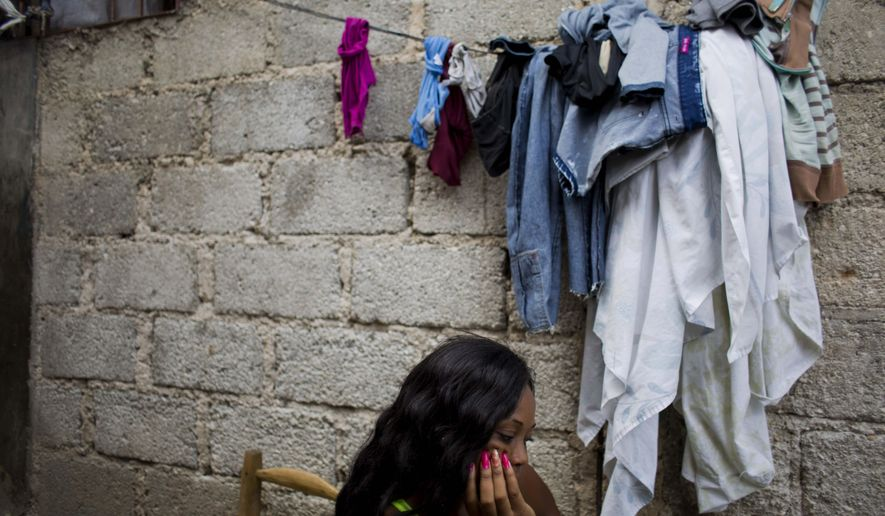 In this Aug. 11, 2016 photo, Lovely Harasme 26, sits in front of her mother's house in Port-au-Prince, Haiti. She says she was one of several women who worked as prostitutes for Sri Lankan peacekeepers with the U.N. (AP Photo/Dieu Nalio Chery)