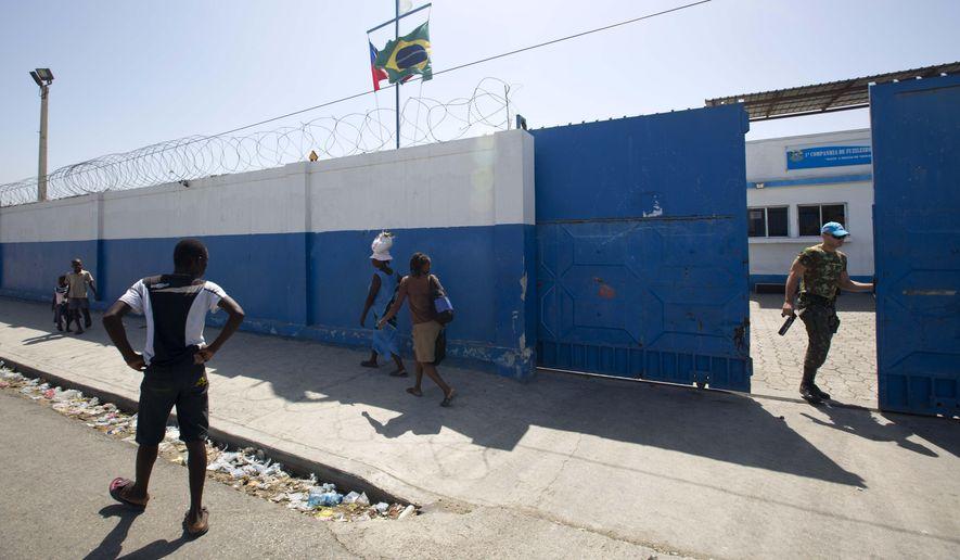 In this Aug. 16, 2016, file photo, a Brazilian U.N. peacekeeper opens a gate at the U.N. base in the Cite Soleil slum of Port-au-Prince, Haiti. (AP Photo/Dieu Nalio Chery) ** FILE **