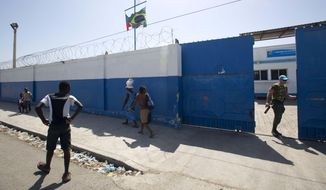 In this Aug. 16, 2016, file photo, a Brazilian U.N. peacekeeper opens a gate at the U.N. base in the Cite Soleil slum of Port-au-Prince, Haiti. (AP Photo/Dieu Nalio Chery) ** FILE **