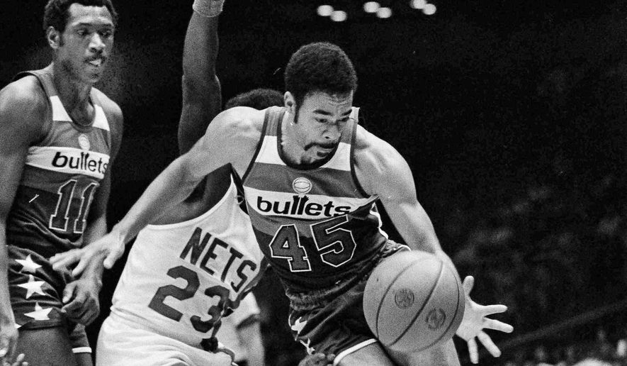 Washington Bullets guard Phil Chenier, right, does a flying turn as he grabs the ball en route to the basket in Uniondale, N.Y., Oct. 28, 1976. On defense for the New York Nets is John Williamson, center, as Bullets Elvin Hayes, left, looks on. The Nets beat the Bullets, 96-93. (AP Photo/Richard Drew) **FILE**
