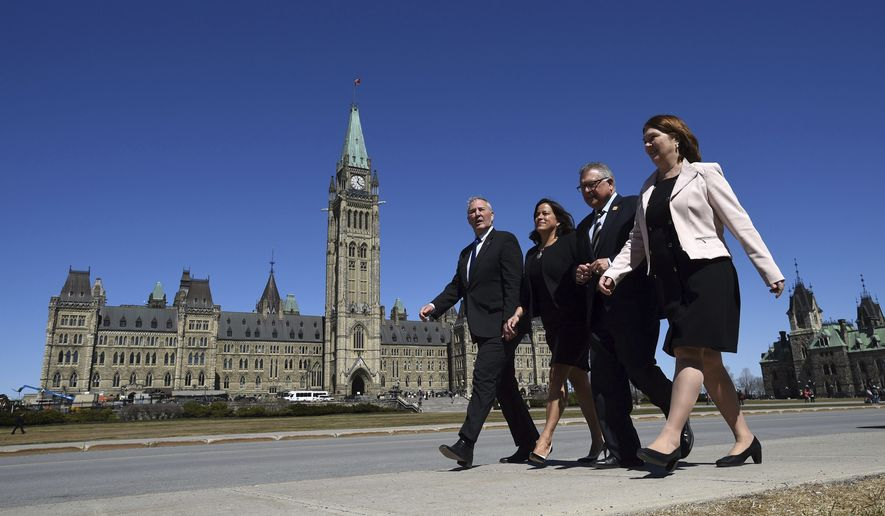 From left to right, Canada's Parliamentary Secretary Bill Blair, Justice Minister and Attorney General of Canada Jody Wilson-Raybould, Public Safety and Emergency Preparedness Minister Ralph Goodale and Health Minister Jane Philpott make their way to the National Press Theatre in Ottawa, Ontario on Thursday, April 13, 2017. Canadian Prime Minister Justin Trudeau's government has introduced legislation to let adults to possess 30 grams of marijuana in public.  (Sean Kilpatrick/The Canadian Press via AP)