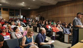 "People crowd the Lansing City Council chambers for a special meeting in Lansing, Mich., Wednesday, April 12, 2017. Michigan's capital city on Wednesday rescinded its decision to deem itself a ""sanctuary city"" protecting immigrants, bowing to concerns from the business community that the ambiguous, contentious term may draw unwanted attention to Lansing. (Matthew Dae Smith/Lansing State Journal via AP)"