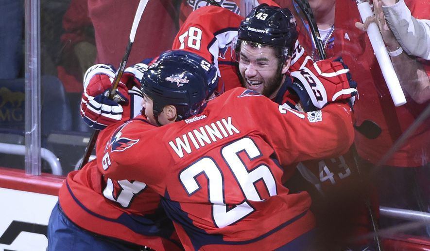 Washington Capitals right wing Tom Wilson (43) celebrates his overtime goal with center Jay Beagle (83) and left wing Daniel Winnik (26) against the Toronto Maple Leafs during Game 1 of an NHL hockey Stanley Cup first-round playoff series in Washington, Thursday, April 13, 2017. The Capitals won 3-2. (AP Photo/Molly Riley)