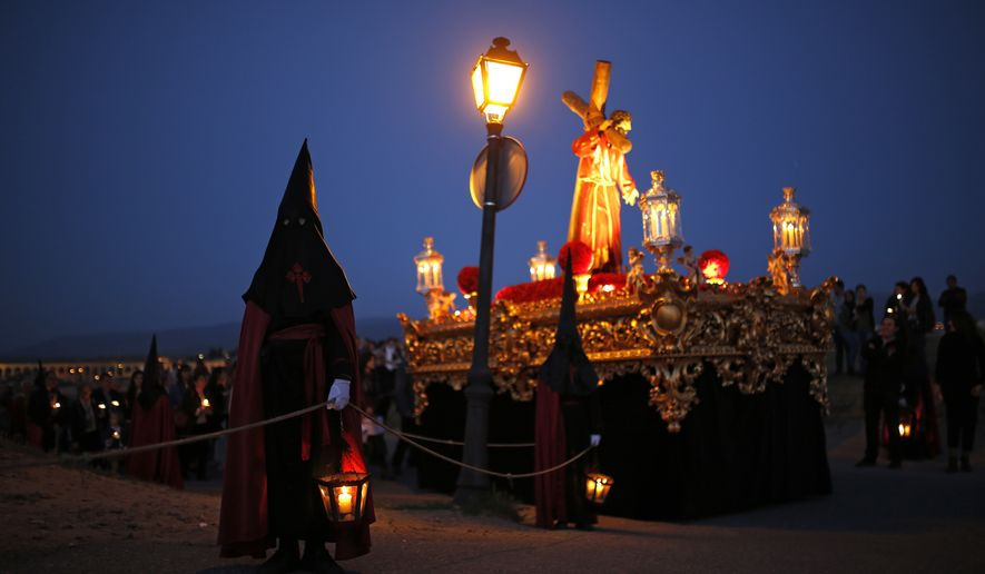 """Hooded penitents from """"Jesus con la Cruz a Cuestas"""" brotherhood hold lanterns with candles they take part in a traditional annual Holy Week procession in Segovia, Spain, Thursday, April 13, 2017. Hundreds of processions take place throughout Spain during the Easter Holy Week. (AP Photo/Francisco Seco)"""