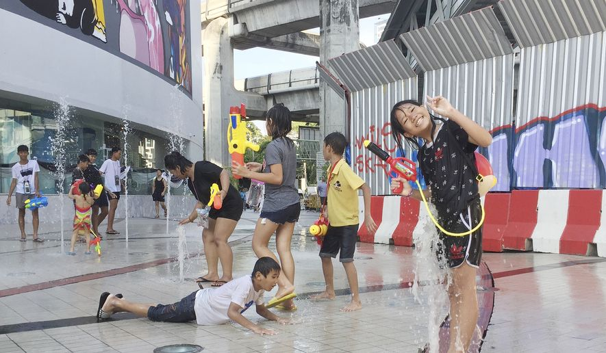 Revelers play in a fountain as they carry water guns while celebrating Songkran, or the Buddhist New Year, in Bangkok, Thursday, April 13, 2017. Locals and visitors are not spared from being doused with water during the three-day national festival throughout Thailand. (AP Photo/Penny Yi Wang)