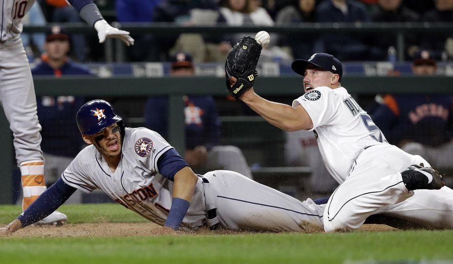 Seattle Mariners relief pitcher Dan Altavilla watches the ball pop loose from his glove as Houston Astros' Carlos Correa scores on a wild pitch during the seventh inning of a baseball game Wednesday, April 12, 2017, in Seattle. (AP Photo/Elaine Thompson)