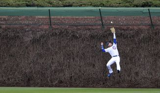 Chicago Cubs center fielder Albert Almora Jr. (5) leaps to make a catch of the ball hit by Los Angeles Dodgers' Corey Seager during the first inning of a baseball game in Chicago, on Thursday, April 13, 2017. (AP Photo/Jeff Haynes)