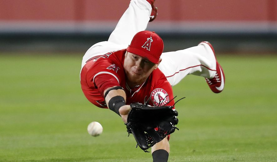 Los Angeles Angels right fielder Kole Calhoun dives for but misses a single by Texas Rangers' Jonathan Lucroy during the eighth inning of a baseball game, Wednesday, April 12, 2017, in Anaheim, Calif. (AP Photo/Ryan Kang)