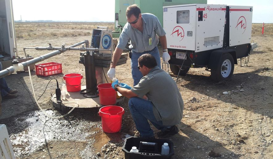 In this July 2013, photo United States Geological Survey scientist Roy Bartholomay, standing, and Flint Hall, with Idaho Department of Environmental Quality, collect a water sample from the Eastern Snake Plain Aquifer at a U.S. Department of Energy nuclear site in eastern Idaho. Scientists said the giant aquifer below an eastern Idaho federal nuclear facility is as free of radioactive contamination and other pollutants as it has been in more than six decades of monitoring but that the water level is at the lowest level ever recorded. (Brian Twining/USGS via AP)
