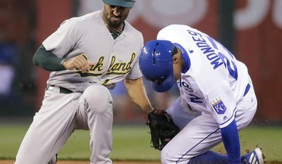 Kansas City Royals' Raul Mondesi (27) beats the tag by Oakland Athletics shortstop Marcus Semien to steal second during the second inning of a baseball game Thursday, April 13, 2017, in Kansas City, Mo. (AP Photo/Charlie Riedel)