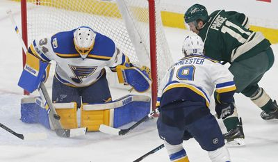 St. Louis Blues goalie Jake Allen, left, stops a shot by Minnesota Wild's Zach Parise, right, during the first period of Game 1 of an NHL hockey first-round playoff series Wednesday, April 12, 2017, in St. Paul, Minn. (AP Photo/Jim Mone)